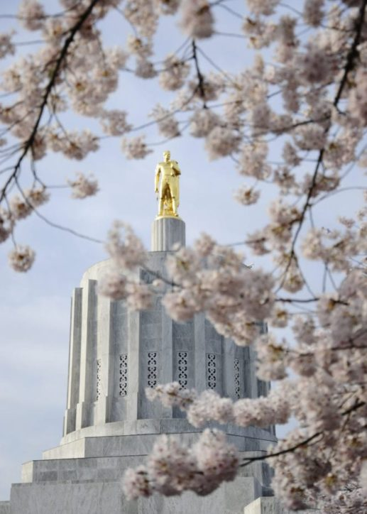 A gold statute of a heroic man stands on top of a marble statue in Salem, a nearby city that is the capital of Oregon.
