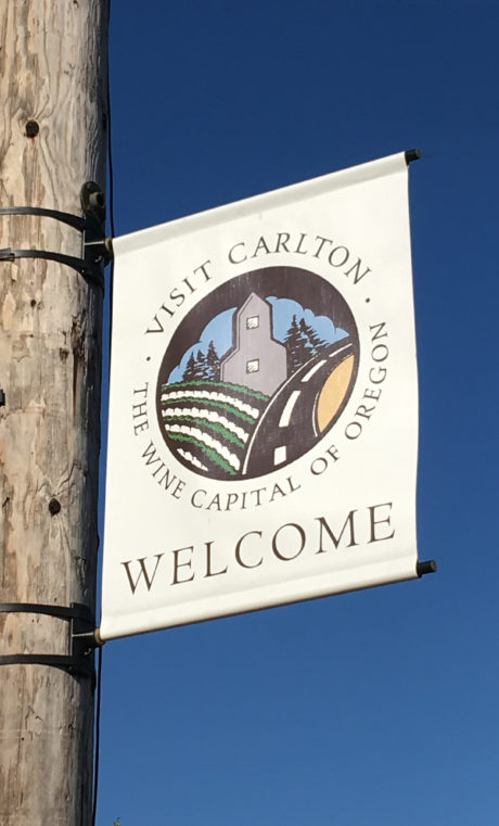A sign on a pole reads Visit Carlton, the Wine Capital of Oregon, Welcome